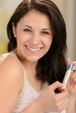 Mujer joven alegre que lleva a cabo la prueba de embarazo Fotografía de archivo libre de regalías