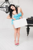 Mujer joven alegre que lleva una maleta en un cuarto ligero Fotos de archivo