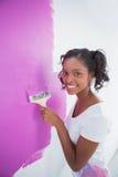 Mujer joven alegre que pinta su pared en rosa Fotos de archivo libres de regalías
