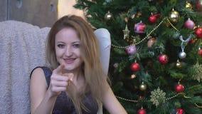 Mujer joven alegre que señala el finger en la cámara en fondo del árbol de navidad almacen de metraje de vídeo