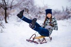 Mujer joven alegre que se divierte en un trineo en invierno Fotos de archivo libres de regalías