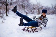 Mujer joven alegre que se divierte en un trineo en invierno Imágenes de archivo libres de regalías