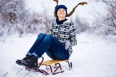 Mujer joven alegre que se divierte en un trineo en invierno Fotos de archivo