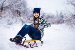Mujer joven alegre que se divierte en un trineo en invierno Foto de archivo libre de regalías