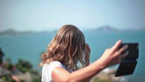 Mujer joven alegre que se divierte que toma imágenes del selfie del smartphone de sí misma en la playa Moda que lleva modelo de l metrajes