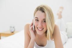 Mujer joven alegre que sonríe en la cámara mientras que llama por teléfono con su smartphone Fotografía de archivo