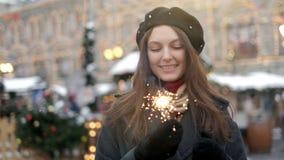 Mujer joven alegre que sostiene bengalas a disposici?n al aire libre Detalle de la muchacha que celebra v?spera del A?o Nuevo s c metrajes