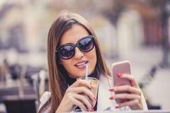 Mujer joven alegre que sostiene el teléfono elegante y que bebe choco caliente foto de archivo