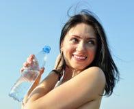 Mujer joven alegre que sostiene la botella de agua fría Fotografía de archivo libre de regalías