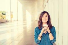 Mujer joven alegre que sostiene la taza de café al aire libre imagen de archivo