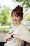 Mujer joven alegre que sostiene una botella de agua Imágenes de archivo libres de regalías