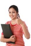 Mujer joven alegre que sostiene una carpeta y que hace el pulgar para arriba imágenes de archivo libres de regalías