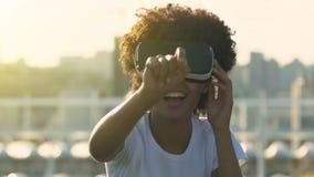 Mujer joven alegre que toca el aire durante la experiencia de la realidad virtual almacen de video
