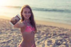 Mujer joven alegre que toma el selfie en la playa arenosa con el mar en el fondo en viaje del día de verano y concepto calientes  Imagen de archivo