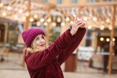 Mujer joven alegre que toma el selfie en el teléfono móvil en la parte posterior Fotografía de archivo