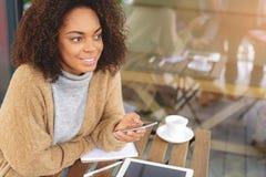Mujer joven alegre que usa un teléfono celular Imagen de archivo libre de regalías