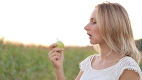 Mujer joven alegre sana que come Apple verde y la sonrisa almacen de metraje de vídeo