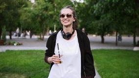 Mujer joven alegre, sonriente que camina al aire libre Estilo ocasional Forme a la muchacha en dunglasses y auriculares negros en almacen de video