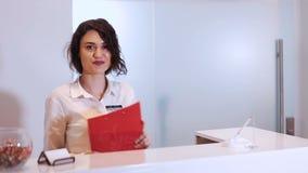 Mujer joven amistosa detrás del administrador del mostrador de recepción metrajes