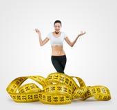 Mujer joven apta con una cinta métrica grande Imágenes de archivo libres de regalías