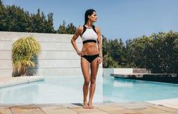 Mujer joven apta en el traje de baño que hace una pausa una piscina Imágenes de archivo libres de regalías