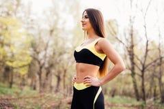 Mujer joven apta en la ropa de deportes que consigue lista para el entrenamiento Mujer sana en parque en un día soleado imagen de archivo