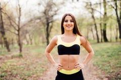 Mujer joven apta en la ropa de deportes que consigue lista para el entrenamiento Mujer sana en parque en un día soleado fotografía de archivo libre de regalías