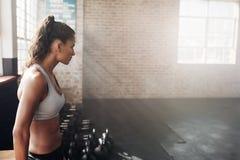 Mujer joven apta en ropa de deportes en el gimnasio fotografía de archivo