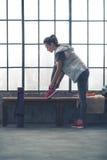 Mujer joven apta que ata el zapato en banco por la ventana en gimnasio del desván de la ciudad Foto de archivo libre de regalías