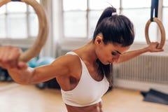 Mujer joven apta que ejercita con los anillos del gimnasta foto de archivo