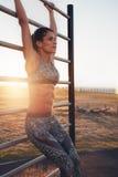 Mujer joven apta que entrena al aire libre en barras de pared foto de archivo libre de regalías