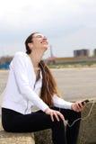 Mujer joven apta que escucha el exterior y la risa de la música Foto de archivo libre de regalías