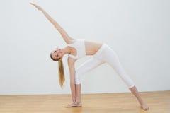 Mujer joven apta que estira su cuerpo en actitud de la yoga Foto de archivo libre de regalías