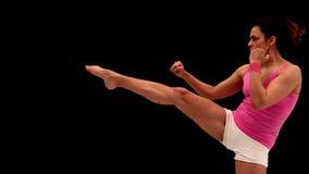 Mujer joven apta que golpea con el pie en fondo negro almacen de video