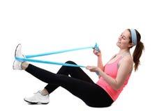 Mujer joven apta que hace entrenamiento con la cinta fisia del látex Imagen de archivo