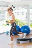 Mujer joven apta que realiza ejercicio de los aeróbicos del paso Foto de archivo