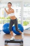 Mujer joven apta que realiza ejercicio de los aeróbicos del paso Foto de archivo libre de regalías