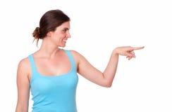 Mujer joven apta que señala a su izquierda Fotos de archivo