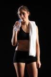 Mujer joven apta que se refresca abajo después de ejercicio Foto de archivo libre de regalías