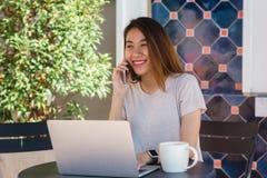 Mujer joven asiática alegre que se sienta en café de consumición del café y que usa el smartphone para hablar, la lectura y manda Imagenes de archivo