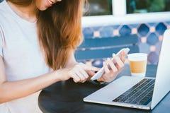 Mujer joven asiática alegre que se sienta en café de consumición del café y que usa el smartphone para hablar, la lectura y manda Fotografía de archivo libre de regalías
