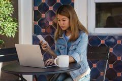 Mujer joven asiática alegre que se sienta en café de consumición del café y que usa el smartphone para hablar, la lectura y manda Imágenes de archivo libres de regalías