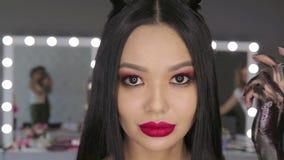 Mujer joven asiática con el lápiz labial brillante que presenta en la cámara metrajes