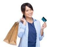 Mujer joven asiática con el panier y la tarjeta de crédito Imágenes de archivo libres de regalías