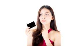 Mujer joven asiática con el vestido rojo que sostiene una tarjeta de crédito Fotos de archivo