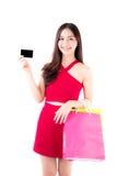 Mujer joven asiática con el vestido rojo que sostiene una tarjeta de crédito y una bolsa de papel imagen de archivo libre de regalías