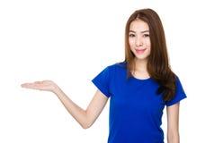 Mujer joven asiática con la mano que muestra la muestra en blanco Fotos de archivo
