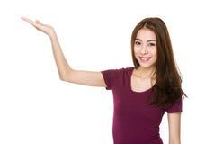 Mujer joven asiática con la palma abierta de la mano para mostrar algo Imagenes de archivo