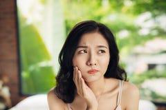 Mujer joven asiática con los dientes dañados en casa Imágenes de archivo libres de regalías