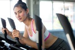 mujer joven asiática de la aptitud en ropa de deportes que ejercita con biking en club del gimnasio del deporte entrenamiento de  fotos de archivo